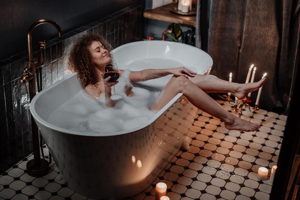 Kvinna i badkar som dricker vin